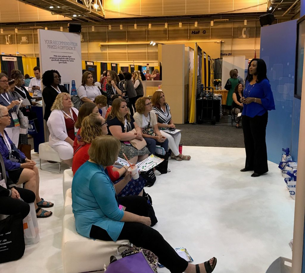 A presenter giving a live presentation to an audience at a trade show